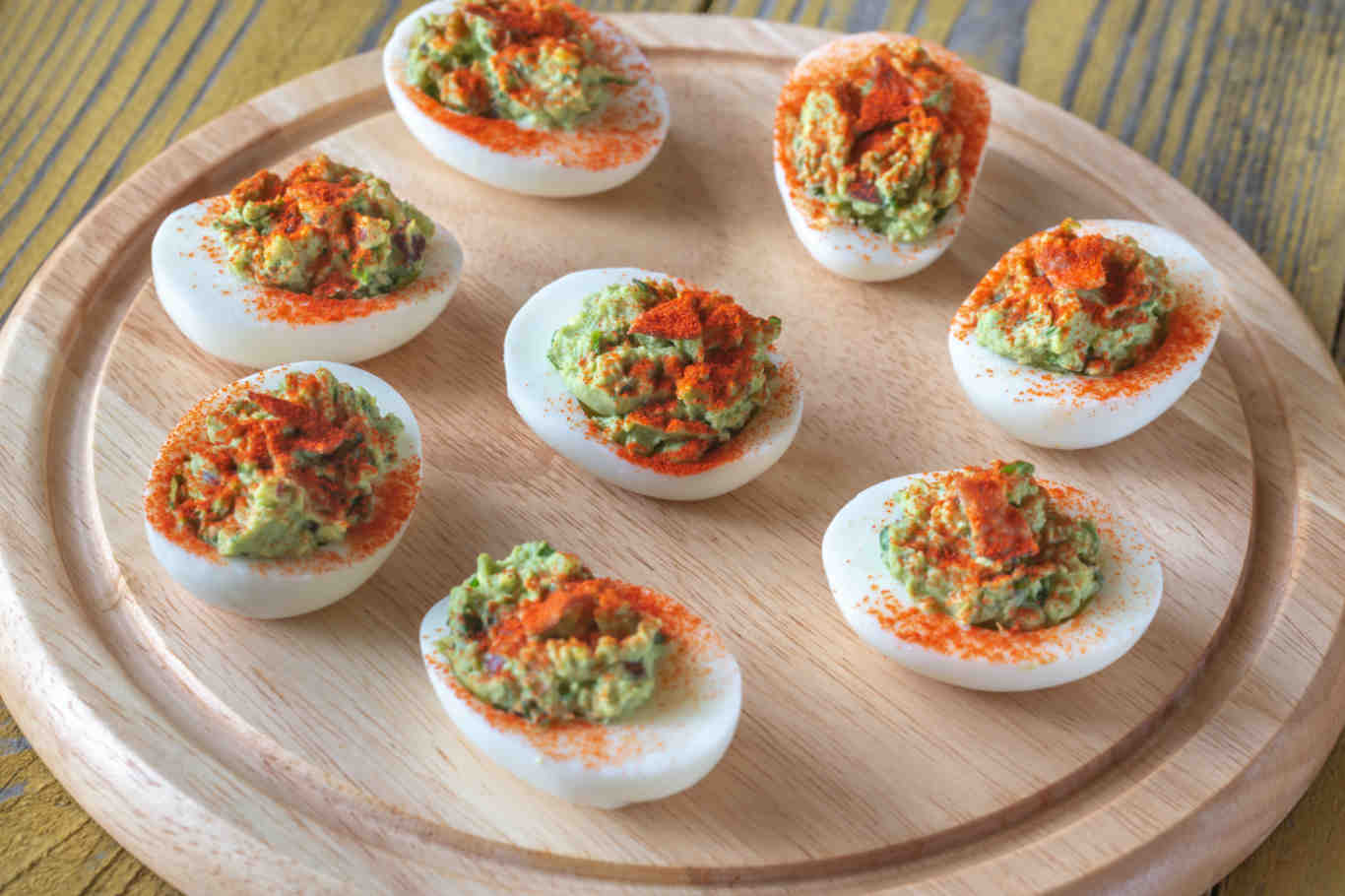 Guacamole and bacon deviled eggs on cutting board