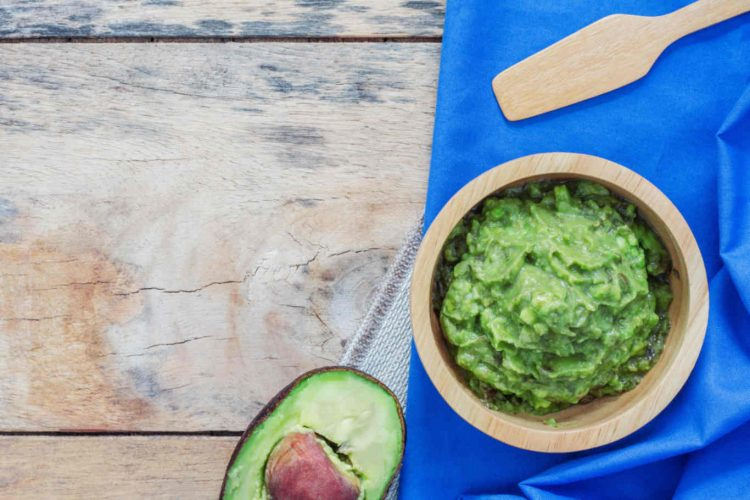 Avocado in a bowl on tablecloth of wood.