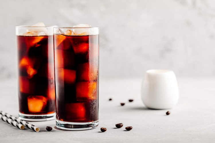 Homemade iced coffee with ice cubes in tall glasses on gray stone background