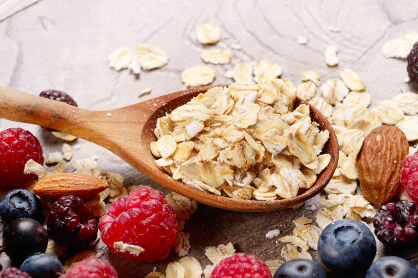 Oatmeal oats with berries and nuts on wooden table
