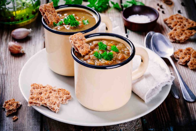 lentil soup with crispbread and parsley in mugs on wooden table