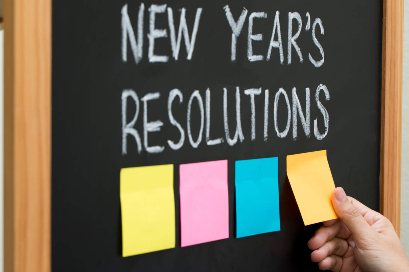 New year resolutions or goals with sticky notes on blackboard